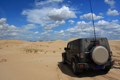 Travelling in the desert. A jeep is exploring in the desert stock photography