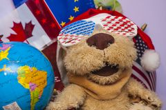 Traveling Dog Stuffed Plush. The stuffed plush dog is looking like a traveler. He has the eyes covered by sunglasses with the American flag. In the background Royalty Free Stock Photography