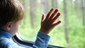 The boy is traveling by train and looks out the window, watching the moving objects outside the window. Hand close-up stock footage