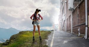 Travelling female tourist with backpack and VR helmet royalty free stock image