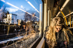 Travelling girl reading the book in the train. Young girl sitting in the train or streetcar watching her smarthone in Norway, Oslo suburb in december 2013 Stock Image