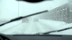 Travelling on the highway in bad weather. Man drives in his car in harsh snowy conditions, with slush, wind and snowfall stock footage