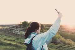 Travelling hiking backpacking sunset selfie sell phone. Side view of the young female hiker with yoga mat and cell-phone doing selfie on the sunset outdoors Royalty Free Stock Photo