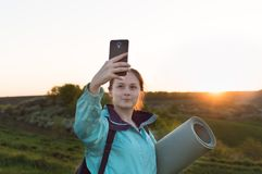 Travelling hiking backpacking sunset selfie sell phone. Young female backpacker with yoga mat and cell-phone doing selfie on the sunset outdoors. Concept of the Royalty Free Stock Image