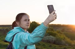 Travelling hiking backpacking sunset selfie sell phone. Young female traveler doing selfie on the sunset outdoors. Concept of the travelling, backpacking, hiking Stock Photography
