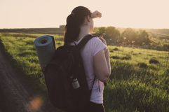 Travelling hiking backpacking sunset success inspiration. Toned photo of the young female traveler with backpack travel mat and vacuum flask looking on the Royalty Free Stock Photo