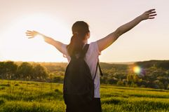 Travelling hiking backpacking sunset success inspiration. Young female with backpack standing outdoors against the sunset. Concept of the travelling, backpacking Stock Image