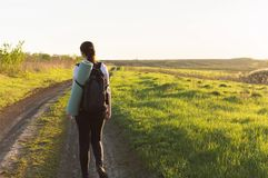 Travelling hiking backpacking sunset success inspiration. Young female hiker with backpack and travel mat going by the dirt road near to the green field. Concept Stock Photo
