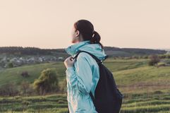 Travelling hiking backpacking sunset tourism. Side view of the backpacker standing on the green hill and looking on the horizon. Concept of the travelling Royalty Free Stock Photography