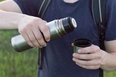 Travelling hiking backpacking sunset tourism. Young male traveller filling the travelling cup with the tea from the vacuum bottle. Concept of the travelling Stock Photography