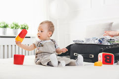 Travelling with kids. Cute toddler packing clothes and toys for holiday Royalty Free Stock Photo