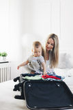 Travelling with kids. Happy mother with her child packing clothes for holiday Royalty Free Stock Photography