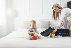 Travelling with kids. Happy mother with her child packing clothes for holiday Royalty Free Stock Photos