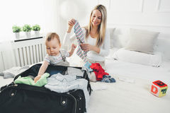 Travelling with kids. Happy mother with her child packing clothes for holiday Royalty Free Stock Photo