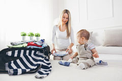 Travelling with kids. Happy mother with her child packing clothes for holiday Stock Image