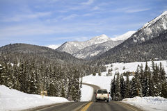 Travelling on a Montana Highway in Winter. A truck travels on a scenic mountain highway in Montana during the winter Royalty Free Stock Images