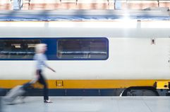 Travelling. A motion blurred woman carrying a luggage walks past a high speed train Royalty Free Stock Image