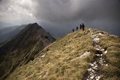 Travelling in the mountains. People on the mountain ridge with a storm approaching royalty free stock photography