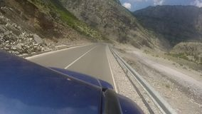 Travelling with off-road vehicle on the curvy mountain highway with 180 degree curve. Beautiful overview over the Albanian Alps mountain stock video footage