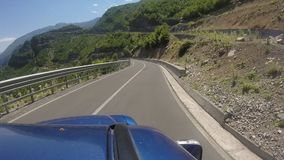 Travelling with off-road vehicle on the curvy mountain highway with 180 degree curve. Beautiful overview over the Albanian Alps mountain stock video