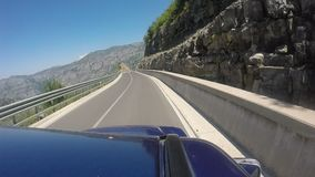 Travelling with off-road vehicle on the curvy mountain highway with 180 degree curve. Beautiful overview over the Albanian Alps mountain stock footage