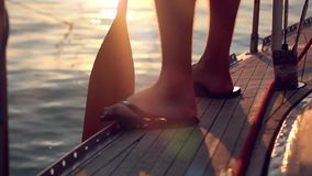 Travelling with the paddle on the boat floats. During sunset. Sunlight reflects in the sea. View on foot men. 1920x1080 stock video