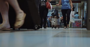 Travelling People with Luggage in Airport. THESSALONIKI, GREECE - AUGUST 2, 2015: Low-angle shot of people in the airport, they are walking through the sliding stock footage