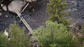 Travelling with ropes for climbing moves in the. The tourist route of the dangerous bridge without railings and fences, in the middle of the Siberian taiga, the stock footage