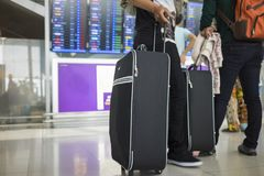 Travelling suitcase against flight information board on background. Concept of travel by airplane.  stock photo