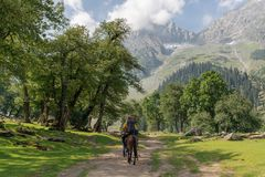 Travelling in summer, backpacker riding horse in summer at Sonamarg, Jammu and Kashmir India. Travelling in summer, backpacker riding horses in summer at royalty free stock photo