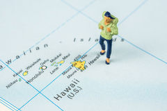 Travelling to Hawaii. Closeup of miniature figurine of young traveller standing on big map next to Hawaii islands Stock Photos