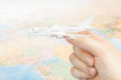 Travelling, tourism, communications and all things related - studio shot of toy aircarft in hand with world map on background Royalty Free Stock Photos