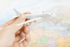 Travelling, tourism, communications and all things related - toy plane in hand with world map on background Royalty Free Stock Photography