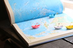Travelling or tourism concept. Travel and tourism concept, paper boats on the map royalty free stock image