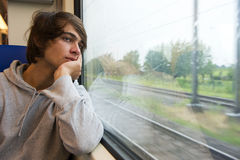 Travelling by train. Bored young man, staring out the train window on a rainy, grey and dull day Stock Images