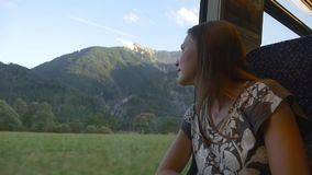Travelling by train in Alps. Relaxed woman looking out of train window on beautiful green summer mountain landscape stock video