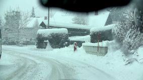 Travelling through the village on a snowy road. Man drives in his car in harsh snowy conditions, with slush, wind and snowfall stock video footage
