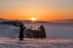 Travelling in winter at lake Baikal in Irkutsk, Russia. Winter landscape in sunset with young woman using mobile smart phone and e. Travelling in winter at lake Stock Images