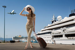 Travelling woman. Stylish slim woman wearing sunglasses and white hat standing in seaport near docked cruise ship while smiling and holding her luggage on a Royalty Free Stock Photo