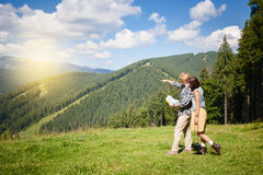Travelling young couple walking on alpine meadow. And looking at the map Royalty Free Stock Photos