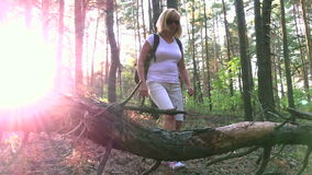 She travels through the woods at sunset. HD stock video footage