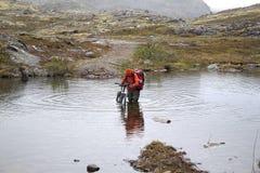 Traverser la rivière à un gué avec une bicyclette Photo stock