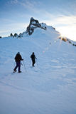 Traversing a Winter Mountain Landscape. A pair of hikers trek across a snowy mountain landscape at sunset stock photography