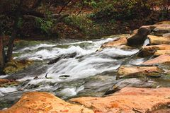 Travertine Creek in Fall. White water cascades over large rocks in a fast running creek with autumn colored trees and leaves. Travertine Creek in the Chickasaw royalty free stock images