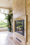 Travertine fireplace next to big window. View of a travertine wall with fireplace next to big window with curtains stock photography