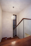 Travertine house - staircase. Travertine house - glass staircase with wooden stairs royalty free stock photography