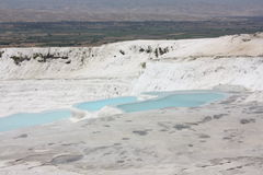 Travertines with blue water in Pamukkale Royalty Free Stock Photo