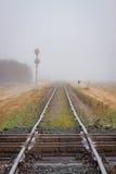 Travesía de dos ferrocarriles con la pista que retrocede en la niebla foto de archivo
