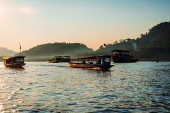 Travesía de la puesta del sol en prabang del luang en el río Mekong La luz suave golpeó los barcos en el agua La mayor parte de e foto de archivo
