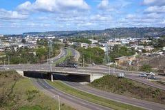 Travesía de las carreteras duales del carril con área industrial Fotografía de archivo